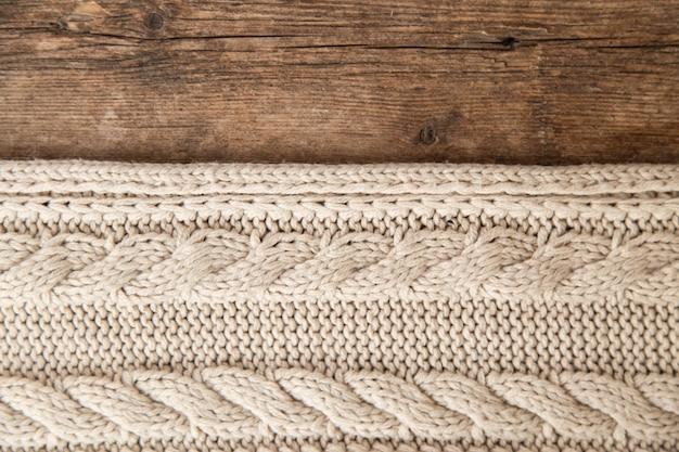 木製の背景にベージュのニットセーターのテクスチャ。ニット、クローズアップ