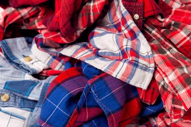 男性の色の服の格子縞のシャツの山