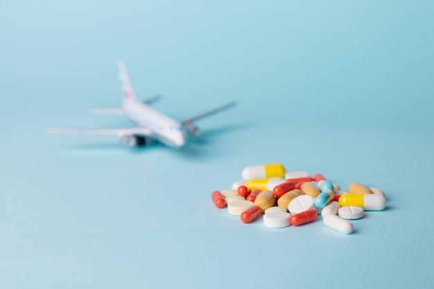 乗り物酔いが散らばって色とりどりの錠剤の飛行機モデル