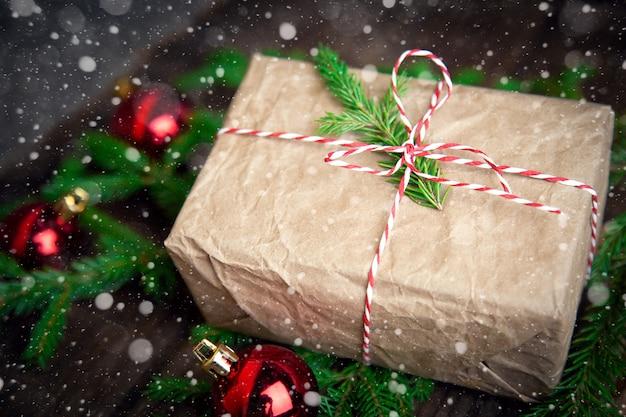 Рождественская композиция вид сверху. подарочная коробка из крафт-бумаги елочные игрушки с шариками, ветки ели со снегом на деревянной