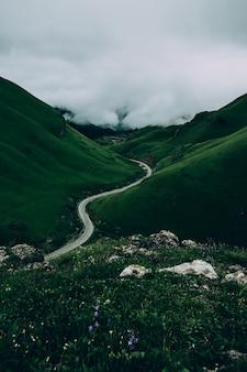 道路は曇りの山の緑の牧草地に囲まれています
