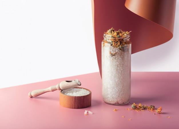 ヒマラヤの塩。バスソルト。スパでのトリートメント。美容およびレジャー産業。ピンクの背景に木製の蓋付きの透明なガラスの瓶に入浴剤の結晶。環境保護、環境に優しいコンセプト