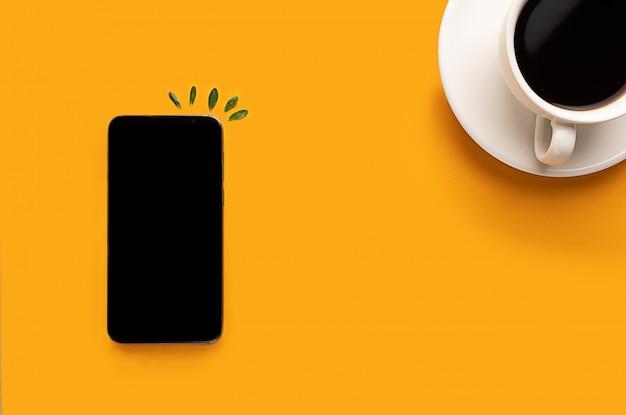 一杯のコーヒーとスマートフォン、コピースペースと黄色の背景に電話。ブロガー、朝食の朝コンセプト。