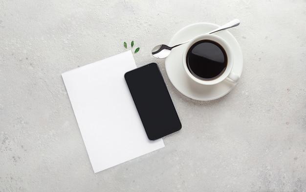 紙、空の空白、メモ帳、ペン、携帯電話、コンクリート、灰色の背景にコーヒーエスプレッソのカップ。計画の概念、リスト、ワークスペース。コピースペースを持つフラットレイアウト。