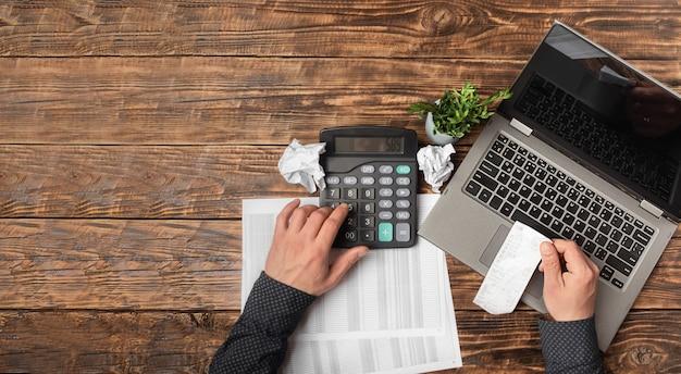 Мужская рука держит чек и использует калькулятор при заполнении индивидуальной налоговой декларации