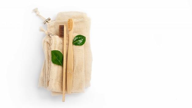Бамбуковые зубные щетки и хлопок сумка на белом фоне с копией пространства. социально-экологическая ответственность. экологичная концепция, ноль отходов, переработка, эко. изолированные