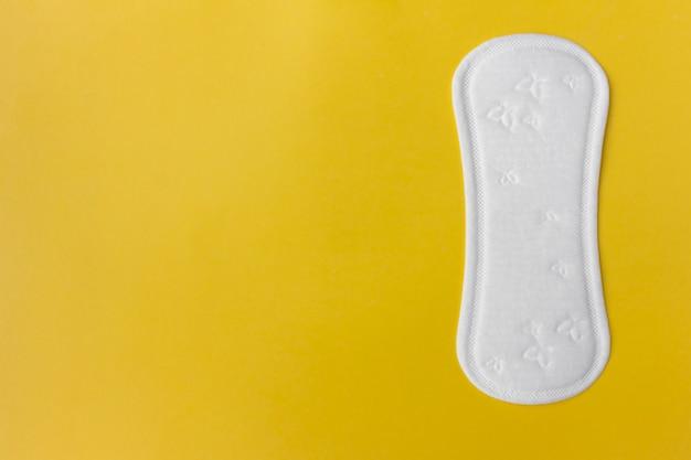 月経中は毎日清潔な白い月経パッド、黄色の上に横たわる、重要な日に女性