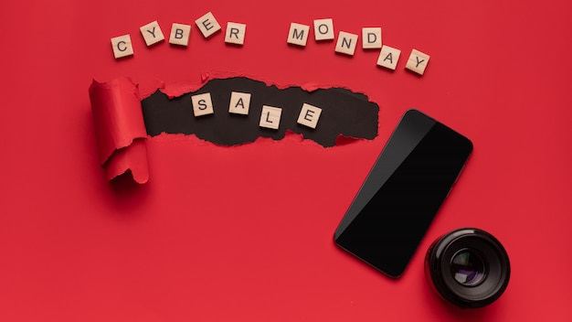 Черная пятница и кибер понедельник, современный смартфон и объектив для камеры на красный и черный.