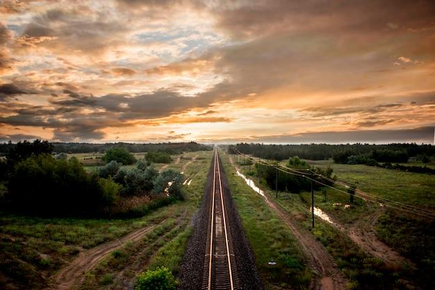 Заход солнца железнодорожного ландшафта природы оранжевый на небе. украина город херсон