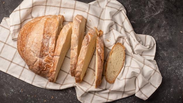 Белый круглый хлеб нарезанный на множество кусочков, расположенный с белой клетчатой салфеткой на черном