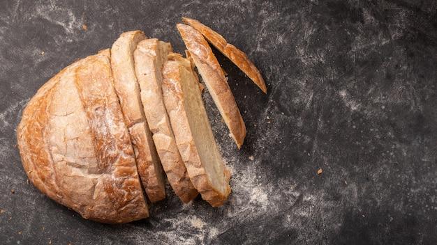 黒に位置する多くの部分にカットされた白い丸いパン