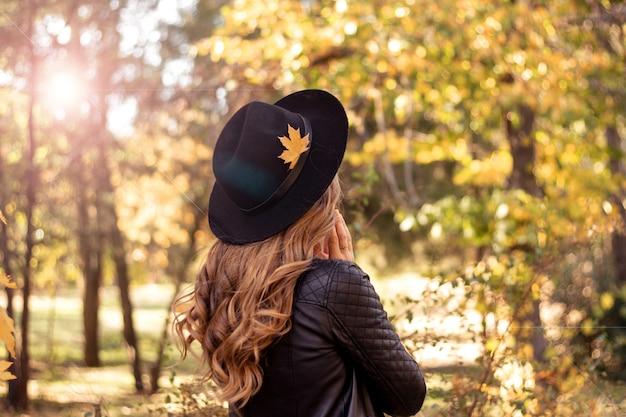 秋のファッションライフスタイルコンセプト。秋の公園を歩いて黒い帽子で自然な金髪の美しい若いヨーロッパの女性