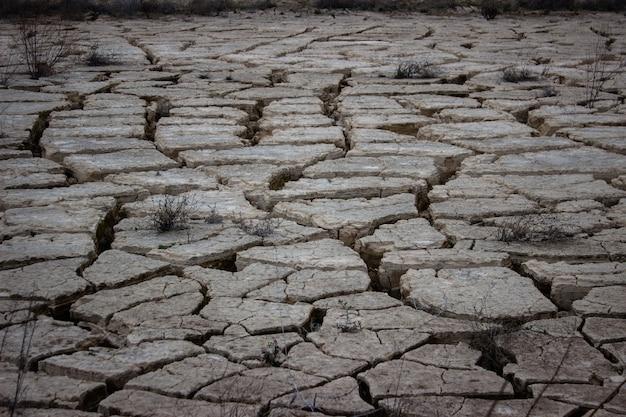 Трещины поверхности пруда во время засухи