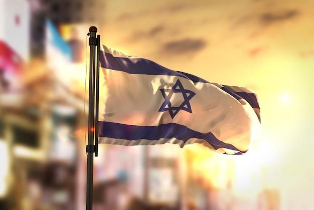 日の出のバックライトで都市のぼやけた背景に対するイスラエルの国旗