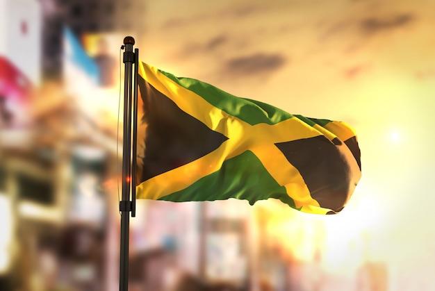 日の出のバックライトで都市のぼやけた背景に対するジャマイカの国旗