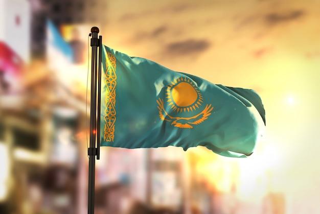 Казахстанский флаг против городского размытого фона при восходе солнца