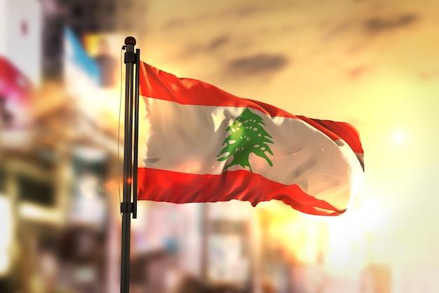 日の出のバックライトで都市のぼやけた背景に対するレバノンの国旗