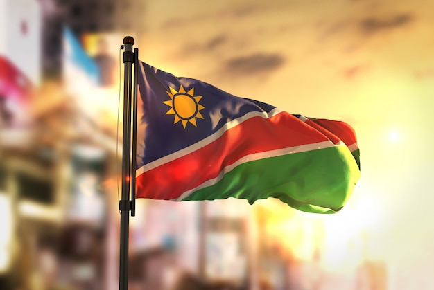 日の出のバックライトで都市がぼやけた背景に対するナミビアの国旗