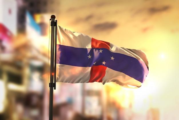 日の出のバックライトで街を曇らせたオランダ領アンティル諸島の旗