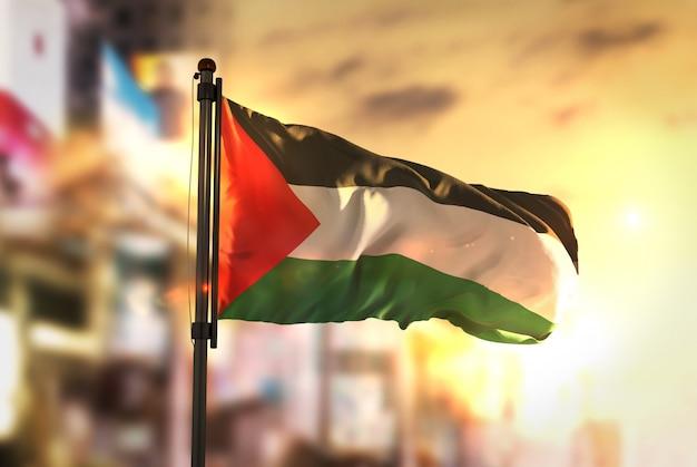 日の出のバックライトで都市をぼやけた背景に対するパレスチナの旗