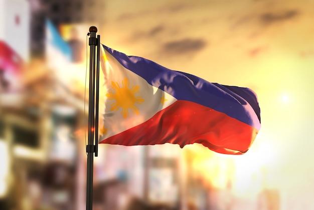 日の出のバックライトで都市がぼやけた背景に対してフィリピンの国旗