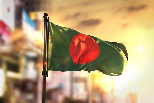 Бангладеш флаг против города размытый фон при восходе солнца