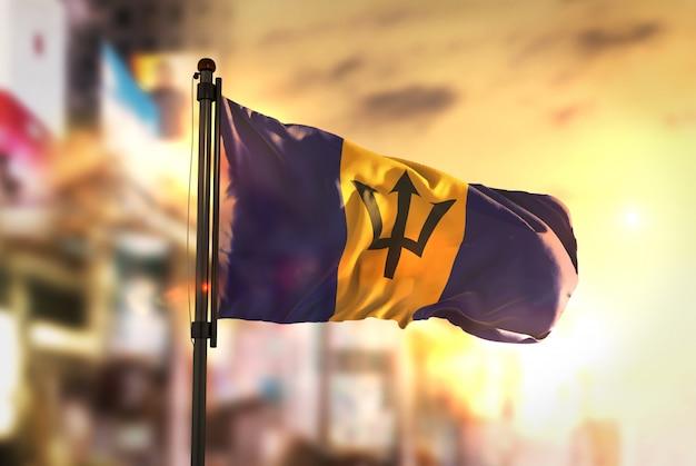 Барбадосский флаг против города размытый фон при восходе солнца