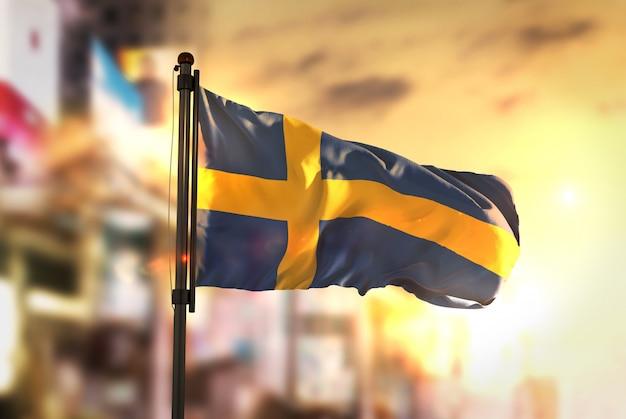 日の出のバックライトで都市がぼやけた背景に対してスウェーデンの国旗