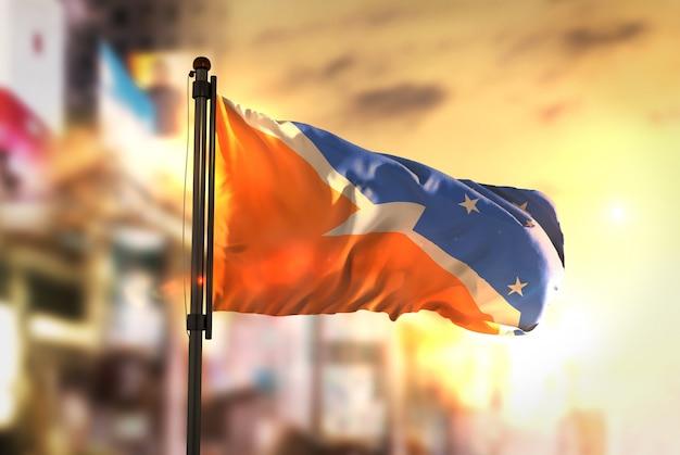 日の出のバックライトで都市のぼやけた背景に対してティエラ・デル・フエゴの国旗