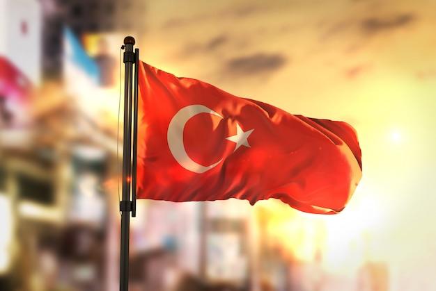 日の出のバックライトで都市のぼやけた背景に対するトルコの国旗