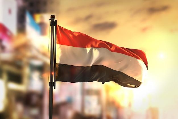 日の出のバックライトで都市のぼやけた背景に対するイエメンの旗