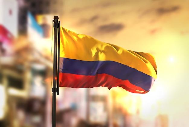 日の出のバックライトで都市のぼやけた背景に対するコロンビアの国旗
