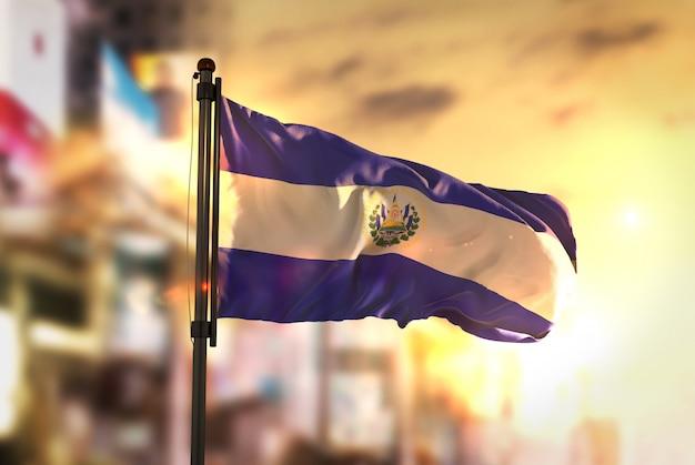 日の出のバックライトで都市のぼやけた背景に対するエルサルバドルの国旗