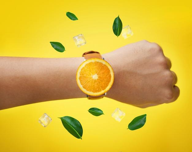 フルーツオレンジ色の腕時計を着用している男性の手緑色の葉とアイスキューブ
