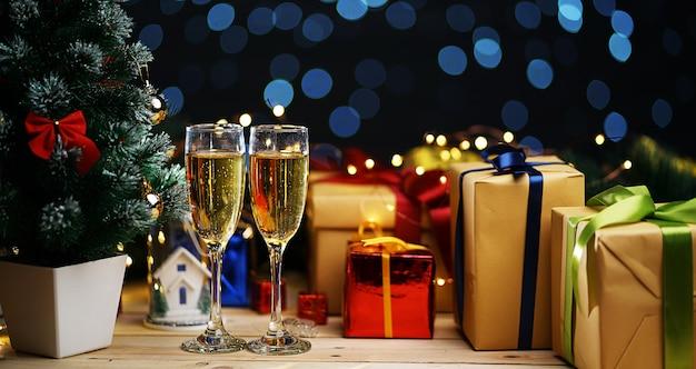 Два стекла шампанского рядом с рождественской елкой и рождественскими подарками