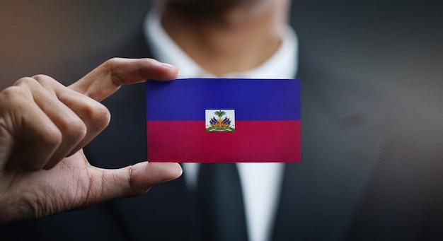 Бизнесмен, держа карты гаити флага