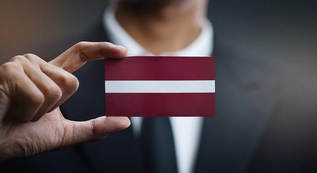 Бизнесмен держит карту флага латвии
