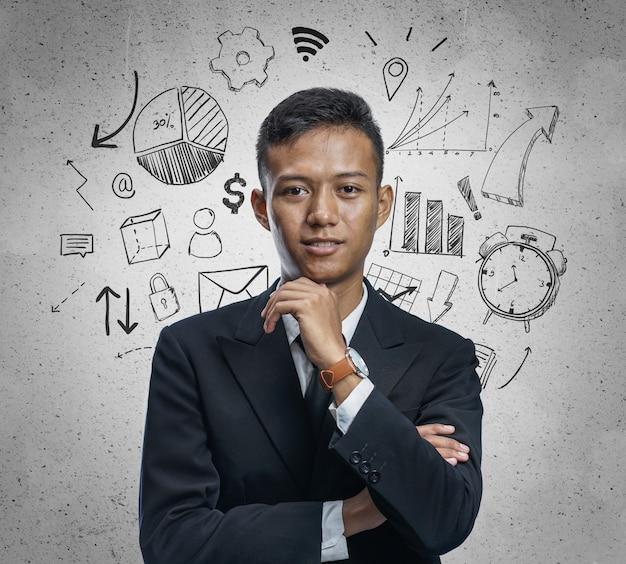 Вдумчивый азиатских бизнесмен, стоя с рукой на подбородке, улыбаясь в бизнес эскиз концепции фон