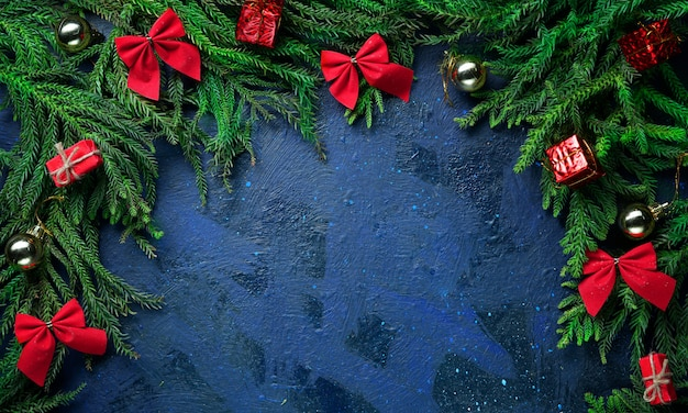 Темно-синий фон пустое пространство. елочные ветки и украшения.