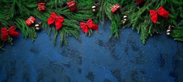 暗い青色の背景の空のスペース。クリスマスツリーの枝と装飾。バナー