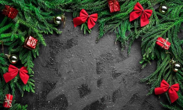 ブラッククリスマスの背景。クリスマスツリーの枝と赤い装飾に囲まれて