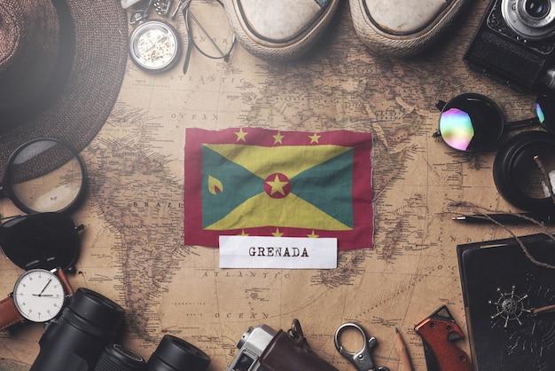 古いビンテージ地図上の旅行者のアクセサリーの間にグレナダの旗。オーバーヘッドショット