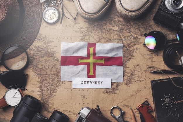 古いビンテージ地図上の旅行者のアクセサリーの間にガーンジーの旗。オーバーヘッドショット