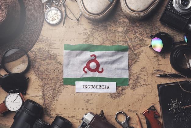 古いビンテージマップ上の旅行者のアクセサリー間のイングーシフラグ。オーバーヘッドショット