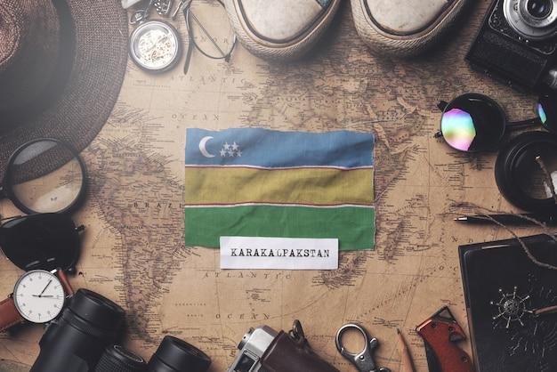 古いビンテージ地図上の旅行者のアクセサリーの間にカラカルパクスタンの旗。オーバーヘッドショット
