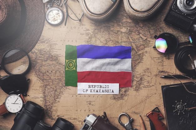 Флаг хакасии между аксессуарами путешественника на старой винтажной карте. верхний выстрел