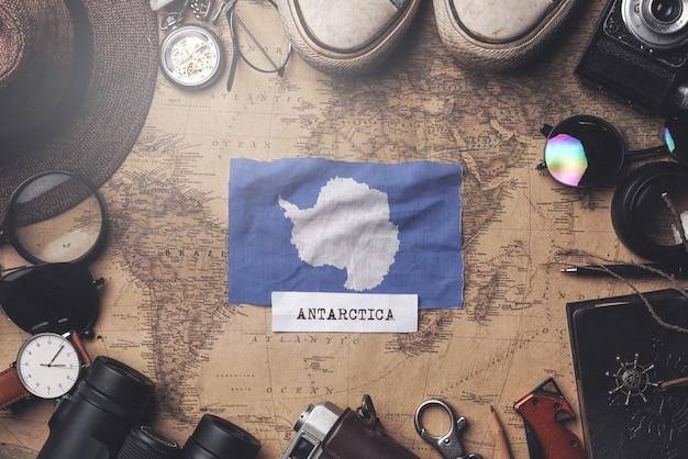 古いビンテージマップ上の旅行者のアクセサリー間の南極大陸の旗。オーバーヘッドショット