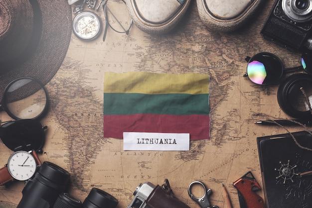 古いビンテージマップ上の旅行者のアクセサリー間のリトアニアの旗。オーバーヘッドショット