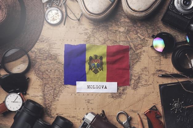 Флаг молдовы между аксессуарами путешественника на старой винтажной карте. верхний выстрел
