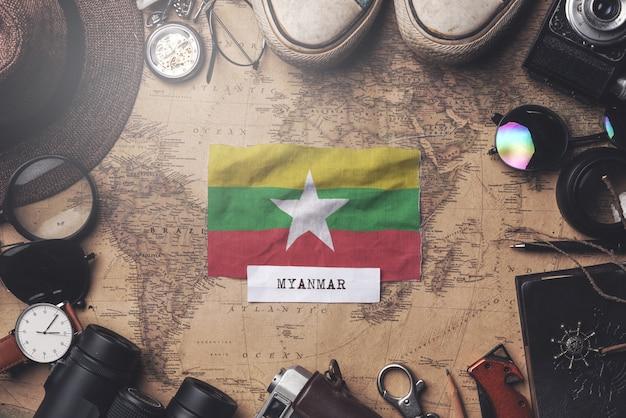 Флаг мьянмы между аксессуарами путешественника на старой винтажной карте. верхний выстрел